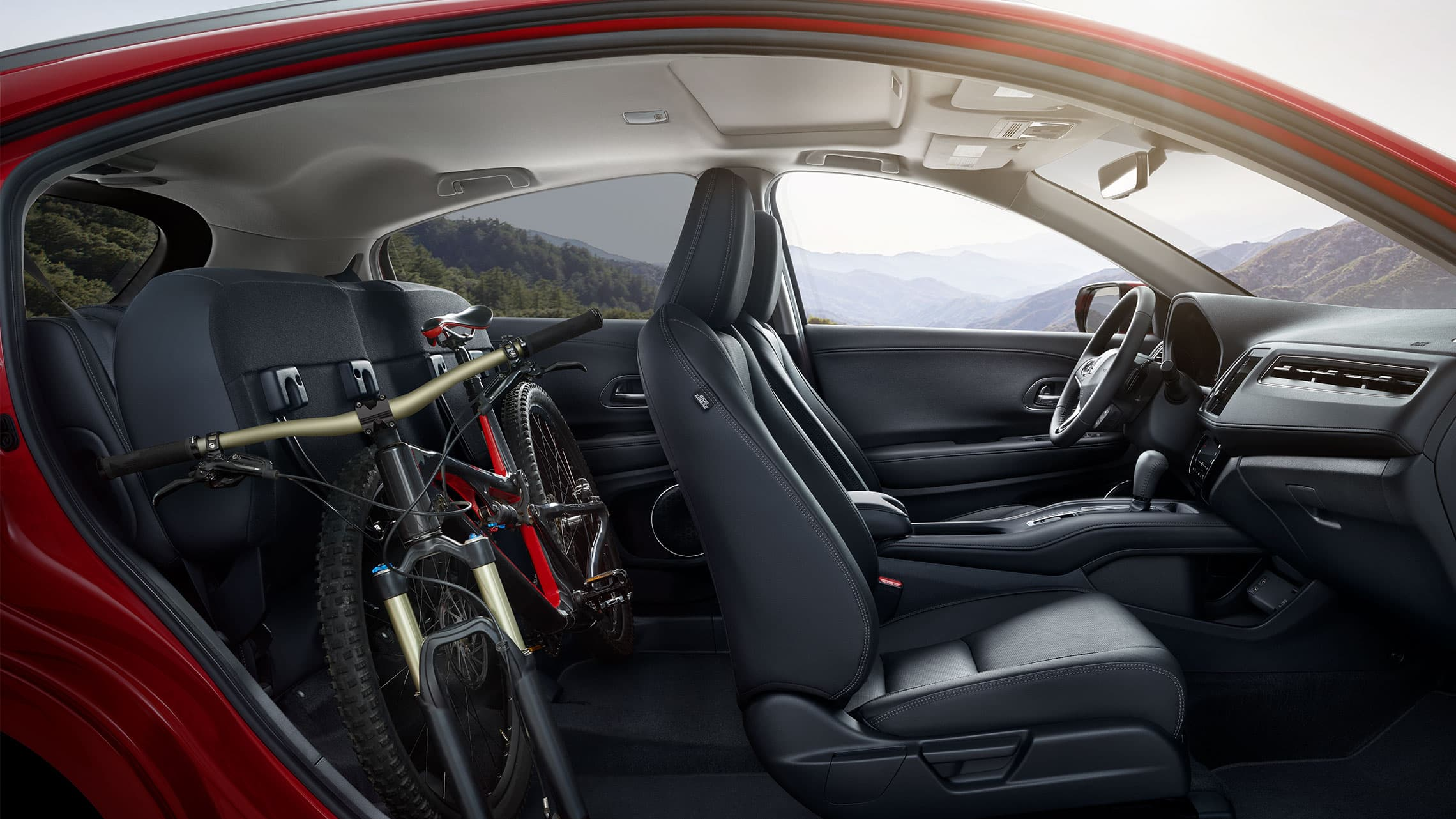 Interior passenger-side view of the 2020 Honda HR-V Touring with Black Leather, with folded rear seats, stowing a bike.